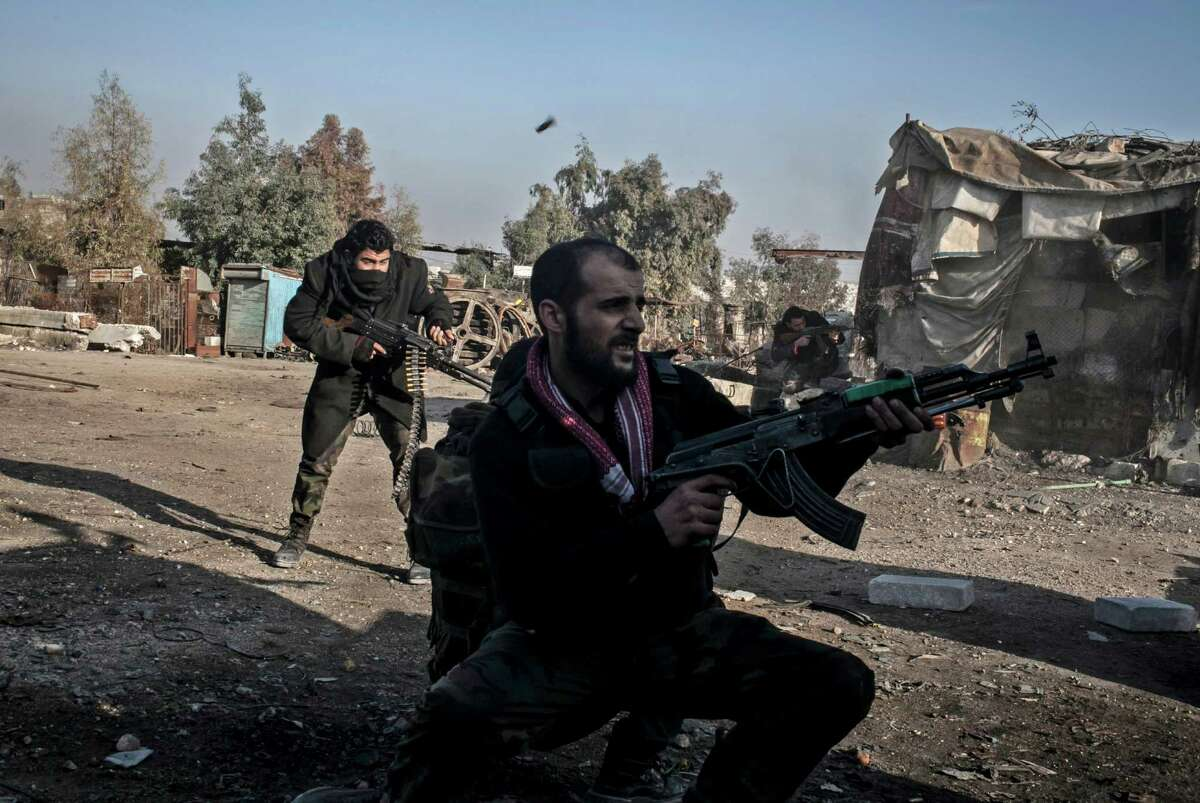 Free Syrian Army fighters fire their weapons during heavy clashes with government forces in Aleppo, Syria, Sunday. The revolt against President Bashar Assad began in March 2011with peaceful protests but morphed into a civil war that has killed more than 60,000 people, according to a recent United Nations recent estimate.