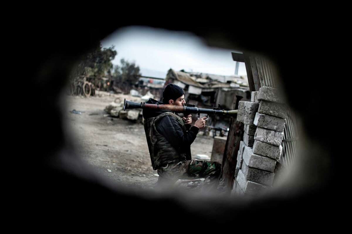 A Free Syrian Army fighter holds his weapon during heavy clashes with government forces in Aleppo, Syria, Sunday. The revolt against President Bashar Assad began in March 2011with peaceful protests but morphed into a civil war that has killed more than 60,000 people, according to a recent United Nations recent estimate.