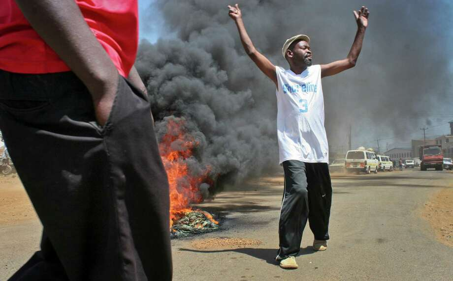 Demonstrators stand near a burning tyre roadblock as they protest the results of the Orange Democratic Movement (ODM) primary elections, after they claimed that Ruth Odinga the younger sister of Kenyan Prime Minister Raila Odinga had been declared the winning ODM candidate for the area's gubernatorial seat, which could not be immediately verified, in the town of Kisumu in western Kenya Sunday, Jan. 20, 2013. Political parties in Kenya this week held their internal elections to decide candidates who will vie for gubernatorial, senate, county, and women representatives seats in the upcoming March 4 elections, a process which was fraught with irregularities, disorganization and disgruntled losers, increasing the chances of conflict during the upcoming vote, analysts said on Friday. Photo: AP