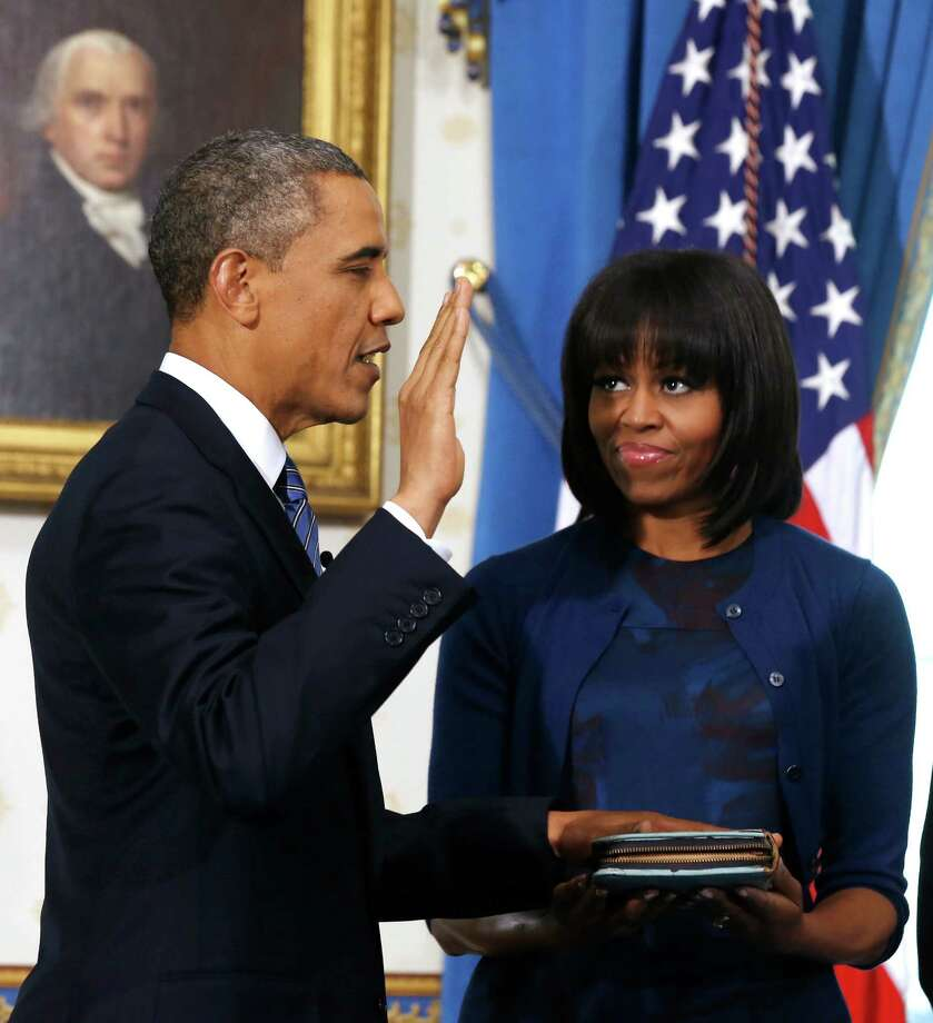 President Barack Obama is officially sworn-in by Chief Justice John Roberts in the Blue Room of the White House during the 57th Presidential Inauguration in Washington on Sunday as first lady Michelle Obama, holds the Robinson Family Bible. Photo: AP
