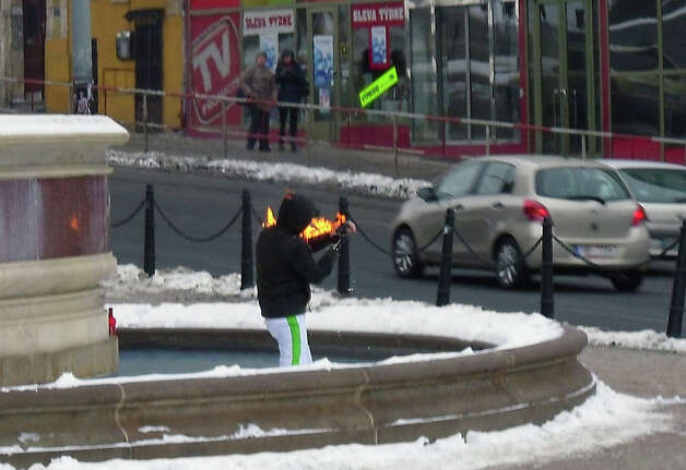 A man sets himself ablaze in Wenceslas Square in the centre of Prague, Czech Republic, Sunday afternoon, Jan. 20, 2013. A passer-by alerted a police patrol. The policemen knocked the man down in the snow and extinguished the fire. For his action, the middle-aged man choose the place near the spot of student Jan Palach's attempted self-immolation in January 1969. He told the police he did not want to commit suicide but only to recall Palach, who killed himself as protest against the invasion of the Warsaw treaty country following the Prague spring. The man suffered lights burns on his hands and was moved to hospital. (AP Photo/CTK, Marion Collinson) SLOVAKIA OUT Photo: AP