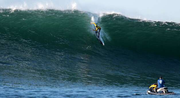 Alex Martins drops into a wave during the finals of the Mavericks Invitational on Sunday, January 20, 2013. Photo: Mathew Sumner, Special To The Chronicle