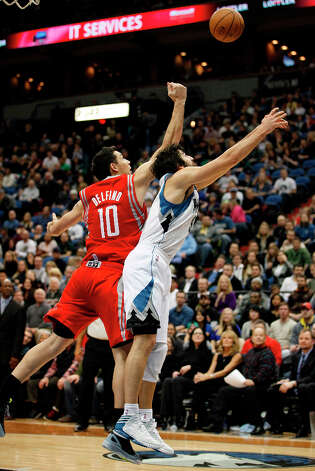 Carlos Delfino of the Rockets and Ricky Rubio of the Timberwolves battle for a rebound. Photo: Stacy Bengs