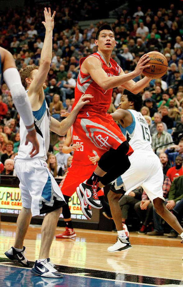 Rockets point guard Jeremy Lin goes to the basket against Luke Ridnour of the Timberwolves. Photo: Stacy Bengs