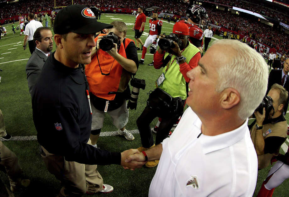 Falcons coach Mike Smith and 49ers coach Jim Harbaugh shake hands after San Francisco topped Atlanta. Photo: Mike Ehrmann / 2013 Getty Images