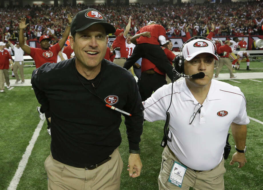 49ers head coach Jim Harbaugh runs onto the field with an assistant after beating the Falcons. Photo: Dave Martin