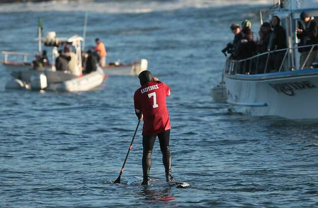 A paddle boarder wearing a Colin Kaepernick jersey combines two big Bay Area sports events. Photo: Mathew Sumner, Special To The Chronicle