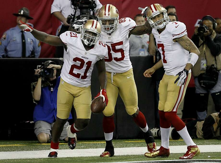 Frank Gore (left), Vernon Davis and Colin Kaepernick - three offensive architects of the victory - celebrate Gore's go-ahead score in the fourth quarter. Photo: Brant Ward, The Chronicle
