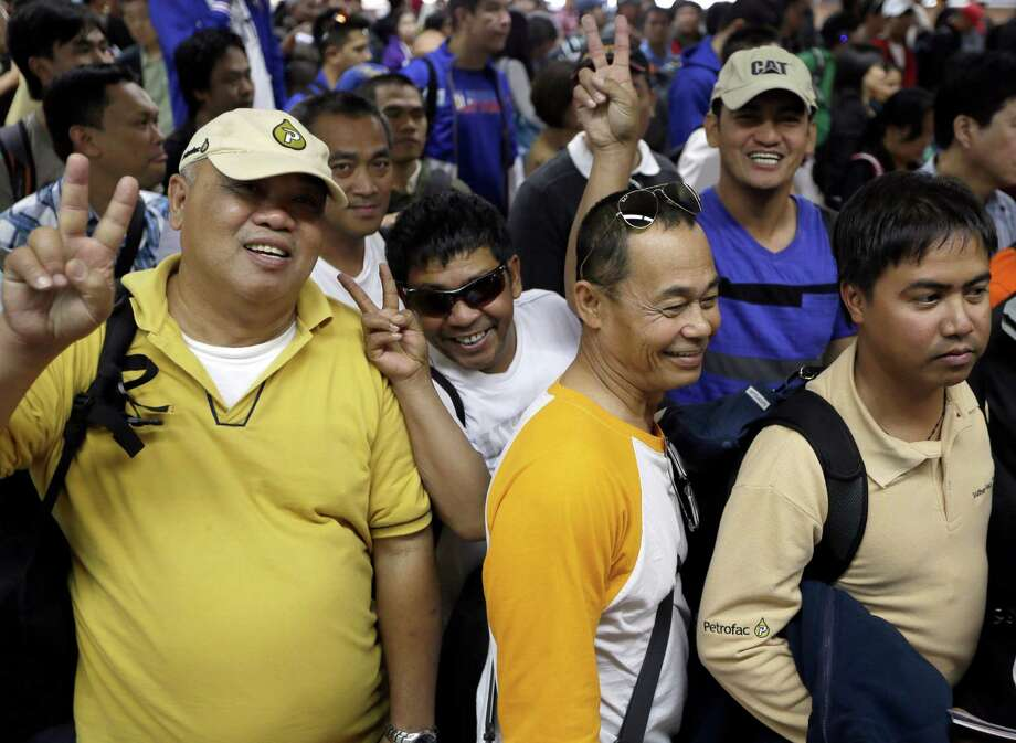 "Overseas Filipinos who were working at the sprawling oil field in Algeria which was attacked by terrorists, flash the ""V"" sign as they queue up at the Philippine Immigration upon arrival Sunday, Jan. 20, 2013 at the Ninoy Aquino International Airport in Manila, Philippines. The Department of Foreign Affairs in their statement, said that 39 Filipino workers, out of the 52 accounted for following the Algerian hostage crisis, arrived after being evacuated from Algeria via Palma de Mallorca in Spain. The workers claimed they were hundreds of kilometers away from the hostage-taking site but ordered evacuated. (AP Photo/Bullit Marquez) Photo: Bullit Marquez, STF / AP"