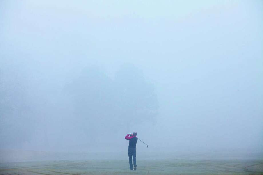 A golfer drives into the fog at the Memorial Park Golf Course Jan. 20, 2013 in Houston. Photo: Eric Kayne, For The Chronicle / © 2013 Eric Kayne