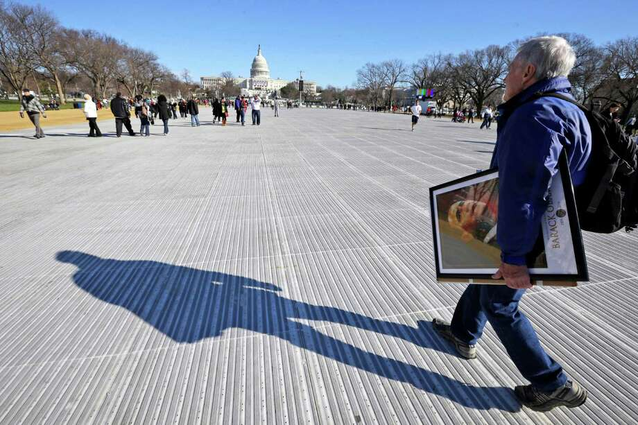 John Osler of Detroit, carries his artwork that is for sale, as he walks on the National Mall Sunday, Jan. 20, 2013, with the U.S. Capitol prepared for ceremonial swearing-in of President Barack Obama, the 57th Presidential Inaugural on Monday in Washington. Photo: Alex Brandon, Associated Press / AP