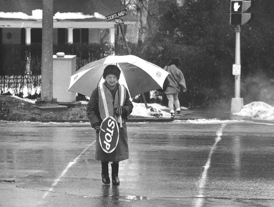 School crossing guard Hortense Sanders survives the rain at Courtland and Hamilton avenues on Jan. 21, 1988. The week before, guards had to deal with snow, ice and bitter cold while helping children cross busy streets. Photo: Advocate