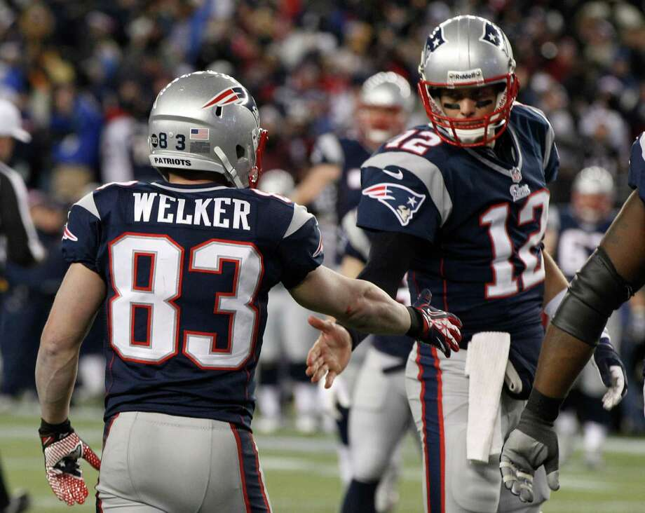 New England Patriots wide receiver Wes Welker (83) is congratulated by Tom Brady after catching a one-yard touchdown pass during the first half of the NFL football AFC Championship football game against the Baltimore Ravens in Foxborough, Mass., Sunday, Jan. 20, 2013. (AP Photo/Stephan Savoia) Photo: Stephan Savoia, Associated Press / AP