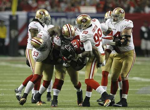 Atlanta Falcons running back Jacquizz Rodgers (32) is picked up and carried back for a loss of yards by Linebacker Aldon Smith (99), Linebacker NaVorro Bowman (53), Defensive tackle Ray McDonald (91) and Defensive tackle Justin Smith (94) in the second half of the San Francisco 49ers game against the Atlanta Falcons in the NFC Championship game at the Georgia Dome in Atlanta, GA., on Sunday January 20, 2013. Photo: Brant Ward, The Chronicle