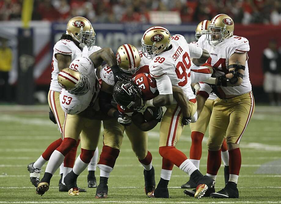 Jacquizz Rodgers is levitated by 49ers, including NaVorro Bowman (53), Ray McDonald (91) and Aldon Smith (99). Photo: Brant Ward, The Chronicle
