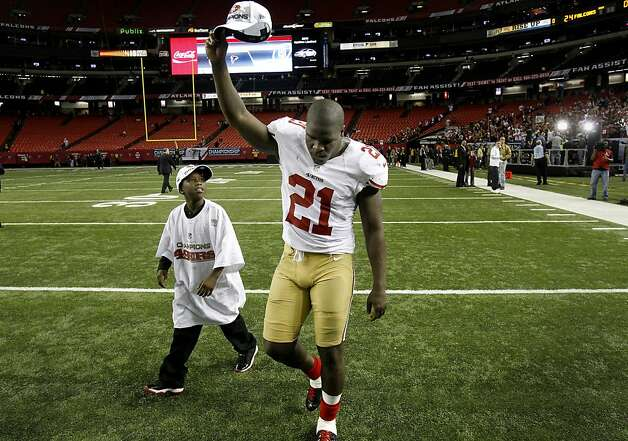 Frank Gore salutes the fans as he walks off the field with his 10-year-old son, known as Little Frank. Gore scored two touchdowns, including the game-winner. Photo: Brant Ward, The Chronicle