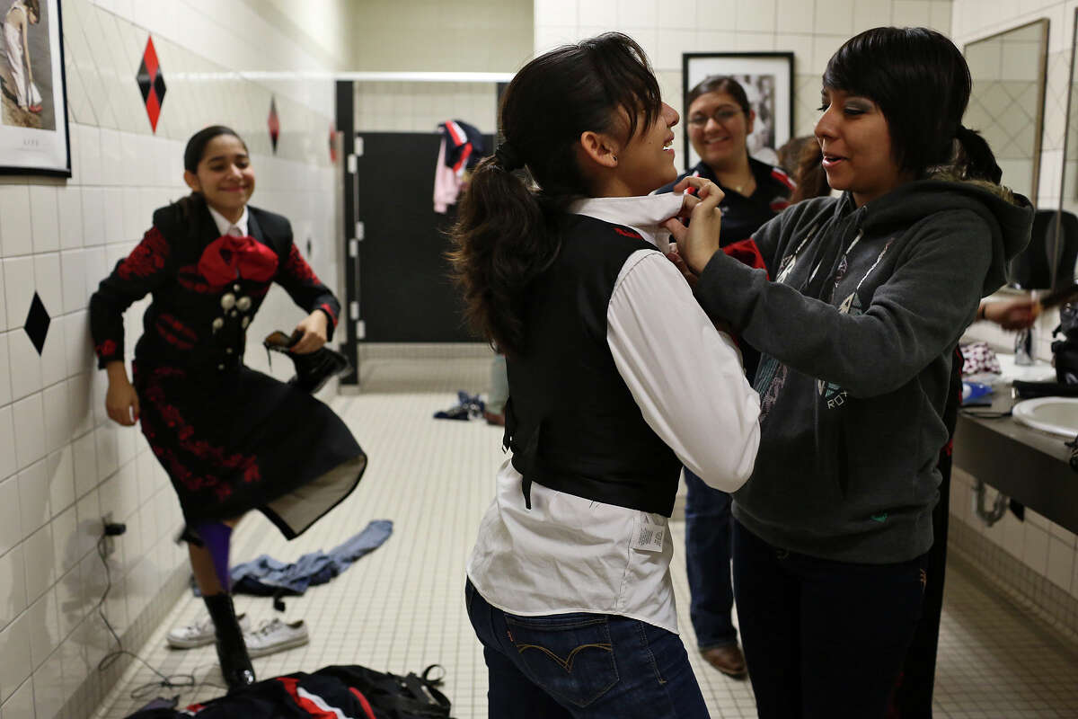 Ashley Diaz, 14, laughs with fellow members of Mariachi Los Lobos, as she realizes her shirt is on inside while they get ready at Palmview High School to perform for the La Joya Independent School District board during a meeting where they were also recognized for their accomplishments on Thursday, Jan. 10, 2013. Helping her adjust her shirt is Rebecca Cano, 16, right, while Ashley's twin, Leslie Diaz, 14, left, and Abigail Aragon, 16, watch.