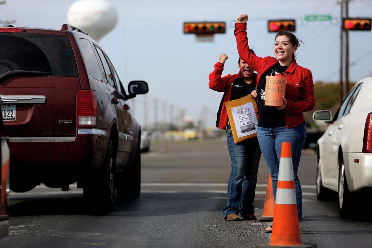 Valeria Gomez, 18, right, and Andrea Martinez, 15, motion for the driver of an 18-wheeler to honk for them as the girls, both members of Palmview High School's Mariachi Los Lobos, and members of Grupo Folklorico Ozomatli collect donations for their trip to perform in the Presidential Inaugural Parade on Saturday, Jan. 12, 2013.