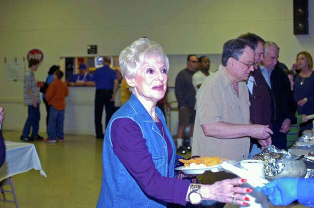 Beaumont resident Gwen Bonsall accepts a fish dinner from a volunteer Sunday at the Knights of Columbus Council 951 Hall. The fish fry, benefiting Boys' Haven, was a joint effort between the Knights of Columbus, Jefferson County Go-Texan and Elks Lodge 311. Photo: Sarah Moore
