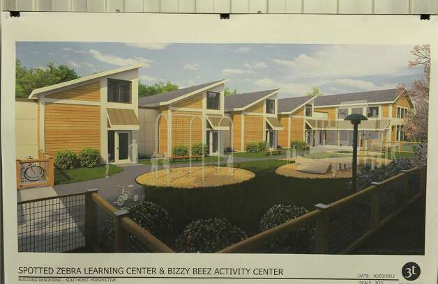An artist drawings of what the  Spotted Zebra Learning Center's new building will look like once it is built, hangs on the wall inside the center on Sunday, Jan. 20, 2013 in Colonie, NY.  Abele, a neighboring business is suing to stop the learning center from building a new center on land near Abele.  (Paul Buckowski / Times Union) Photo: Paul Buckowski