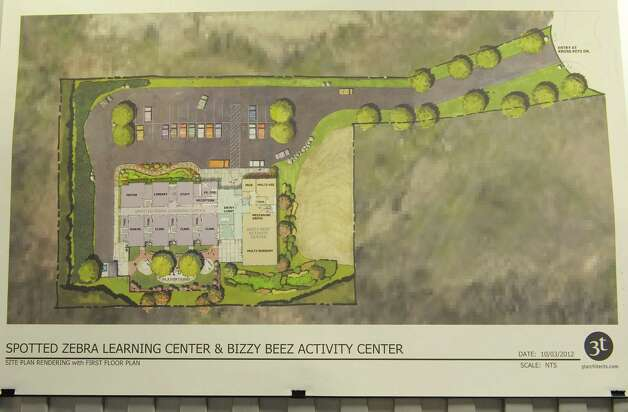 An artist drawings of what the  Spotted Zebra Learning Center's new building will look like from above once it is built, hangs on the wall inside the center on Sunday, Jan. 20, 2013 in Colonie, NY.  Abele, a neighboring business is suing to stop the learning center from building a new center on land near Abele.  (Paul Buckowski / Times Union) Photo: Paul Buckowski