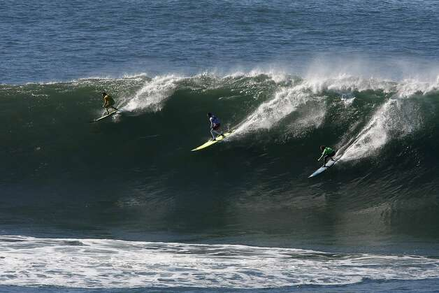 "Colin Dwyer, Anthony Tashnick and Grant ""Twiggy"" Baker all get on the same wave at Mavericks Surf Competition on January 20, 2013 in Half Moon Bay, Calif. Photo: Sean Havey, The Chronicle"