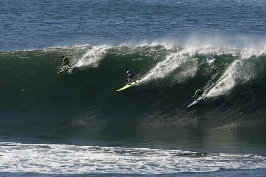 """Colin Dwyer, Anthony Tashnick and Grant """"Twiggy"""" Baker all get on the same wave at Mavericks Surf Competition on January 20, 2013 in Half Moon Bay, Calif. Photo: Sean Havey, The Chronicle"""