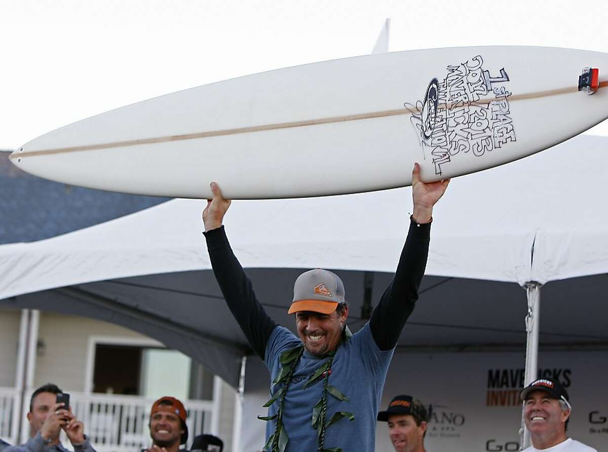 Peter Mel holds up his Jeff Clark surfboard trophy after winning Mavericks Surf Competition on January 20, 2013 in Half Moon Bay, Calif.
