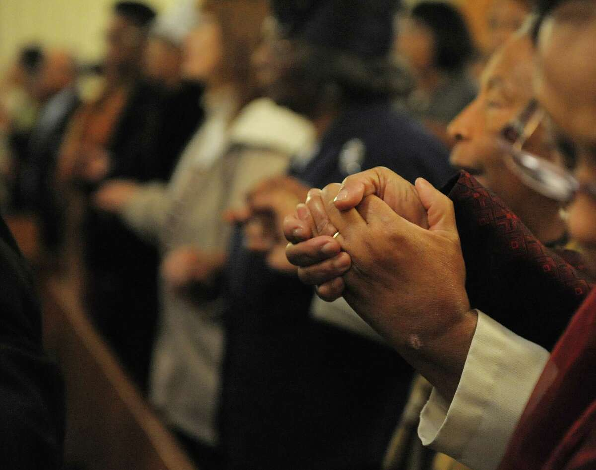 Worshipers hold hands as they sing