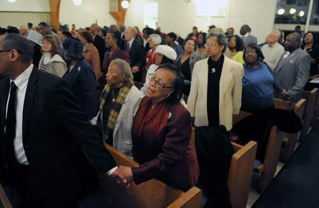 "Maggie Terrell, center, of Albany, holds hands with fellow worshipers as they sing ""We Shall Overcome"" at an interfaith worship service at Bethel Baptist Church to celebrate the Rev. Dr. Martin Luther king, Jr. on Sunday, Jan. 20, 2013 in Troy, NY.  The offering at the service raised money for the Rev. Dr. Martin Luther king, Jr. Scholarship Fund for Troy area youth or adults who wish to pursue advanced education.  Over $1,800 was raised through the offering. (Paul Buckowski / Times Union) Photo: Paul Buckowski"