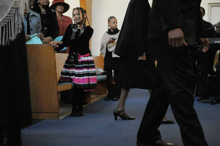 Alexis Shelton, left, 7, from Meands and her older sister Arica Shelton, background, 9, stand as members of the choir and clergy members process in at the start of an interfaith worship service at Bethel Baptist Church to celebrate the Rev. Dr. Martin Luther king, Jr. on Sunday, Jan. 20, 2013 in Troy, NY.  The offering at the service raised money for the Rev. Dr. Martin Luther king, Jr. Scholarship Fund for Troy area youth or adults who wish to pursue advanced education.  Over $1,800 was raised through the offering. (Paul Buckowski / Times Union) Photo: Paul Buckowski
