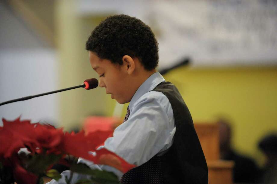 "Decillius Blankenship, Jr. of Troy reads a excerpt from Dr. King's ""I have a dream"" speech at an interfaith worship service at Bethel Baptist Church to celebrate the Rev. Dr. Martin Luther king, Jr. on Sunday, Jan. 20, 2013 in Troy, NY.  The offering at the service raised money for the Rev. Dr. Martin Luther king, Jr. Scholarship Fund for Troy area youth or adults who wish to pursue advanced education.  Over $1,800 was raised through the offering. (Paul Buckowski / Times Union) Photo: Paul Buckowski"