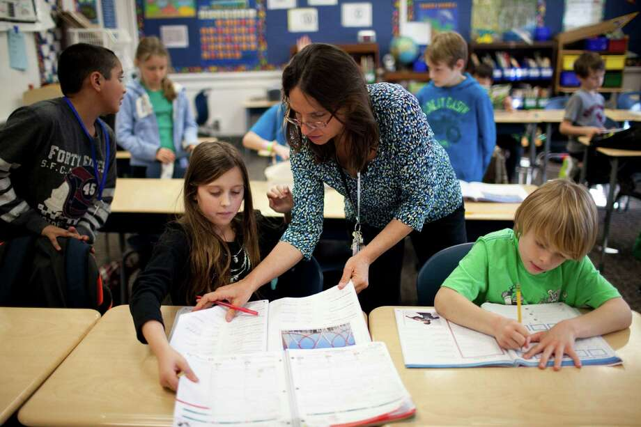 Third grade teacher Elana Spector looks over the cursive work of Maya Archer, 9, at West University Elementary School. Photo: Eric Kayne / © 2013 Eric Kayne