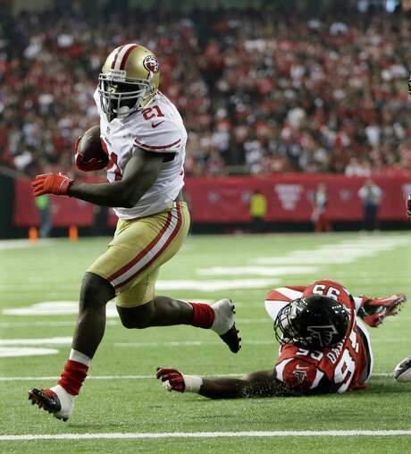 49ers running back Frank Gore scoots away from the Falcons' Jonathan Babineaux to score one of his two second-half touchdowns that allowed San Francisco to turn a 24-14 halftime deficit into a 28-24 victory. Photo: Mark Humphrey, STF / AP
