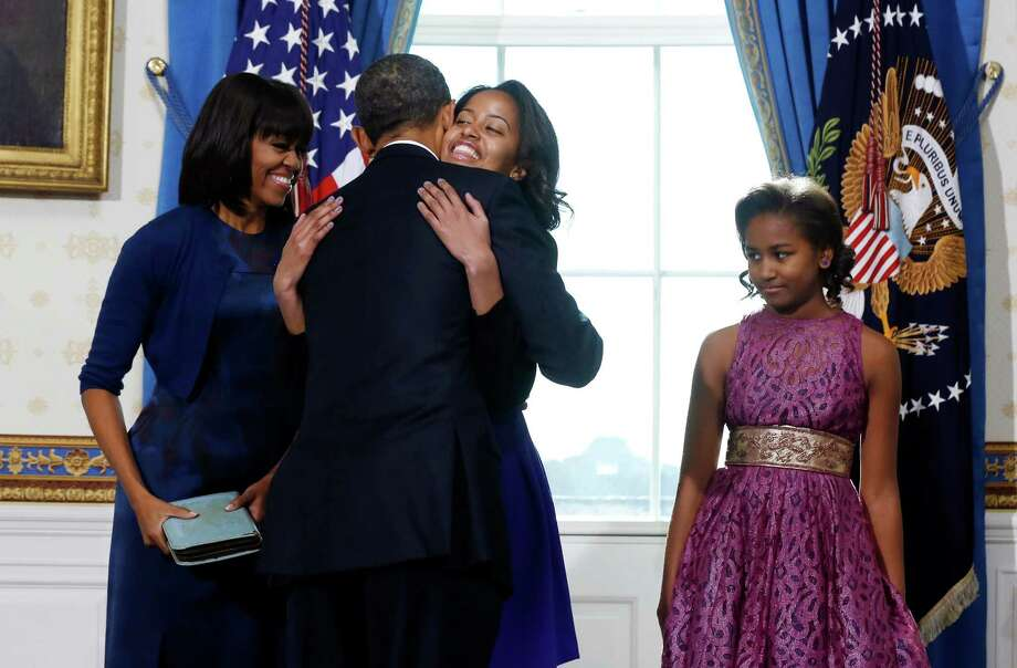 President Barack Obama celebrates after being officially sworn in Sunday with a hug from daughter Malia as wife Michelle and daughter Sasha watch in the Blue Room of the White House. Photo: LARRY DOWNING, POOL / Pool Reuters