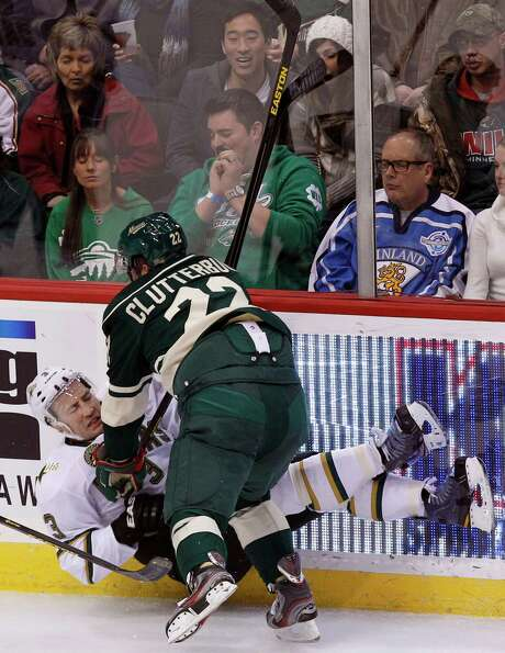 Wild right wing Cal Clutterbuck (22) knocks Stars defenseman Stephane Robidas (3) off his feet during the first period of the Wild's shutout victory Sunday. Photo: Genevieve Ross, FRE / FR170496 AP