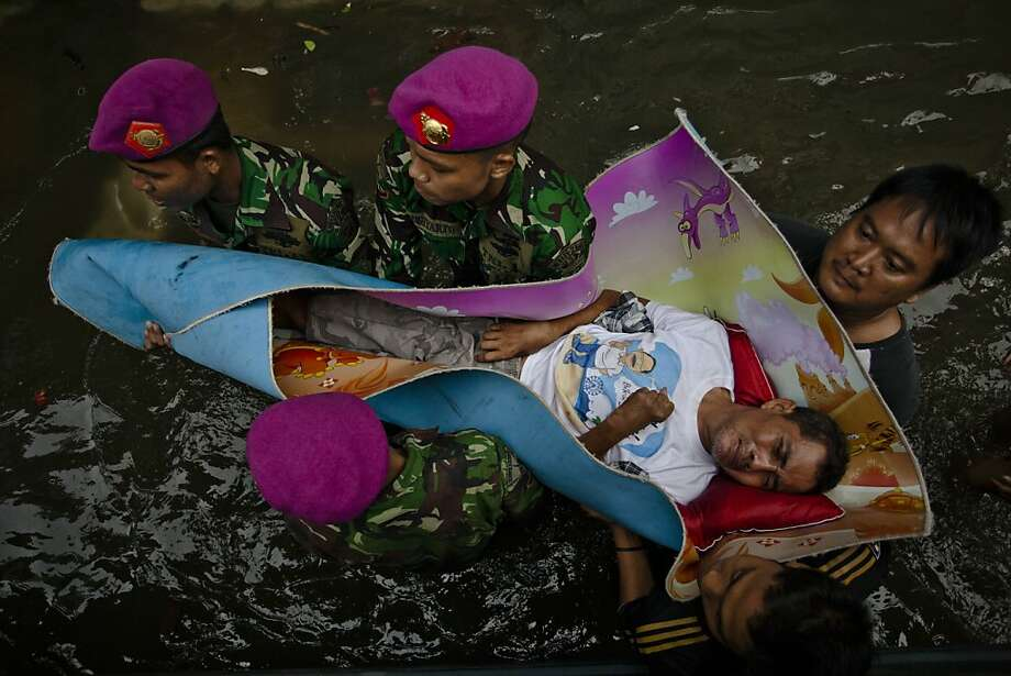 Jakarta under water:Indonesian soldiers carry a man named Syamsuri wrapped in a rug during a flood evacuation in North Jakarta. At least 26 people have died in a week of severe flooding, and thousands have fled their homes. Photo: Ulet Ifansasti, Getty Images