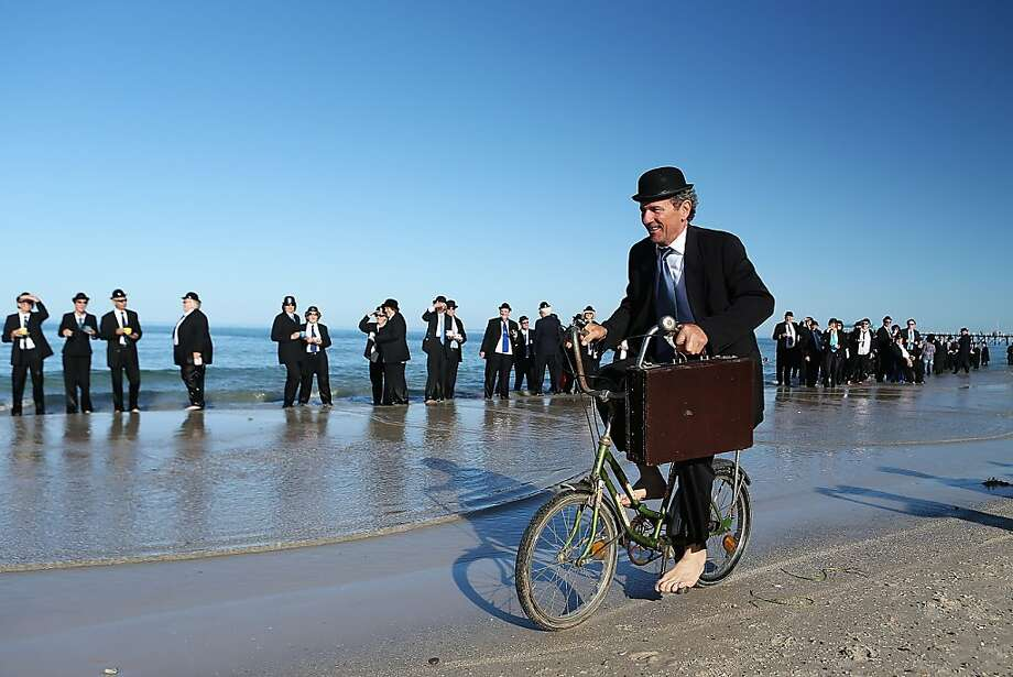 (EDITORS NOTE: A polarizing filter was used for this image.)  A man rides his bicycle on the beach while taking part in an art installation created by surrealist artist Andrew Baines on January 20, 2013 in Adelaide, Australia. Photo: Morne De Klerk, Getty Images