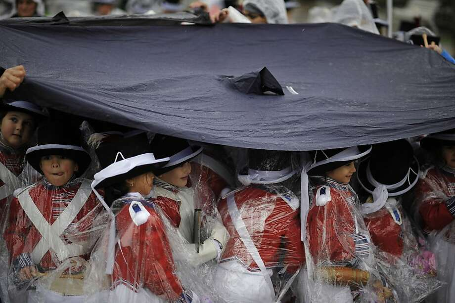 ''Tamborilleros'' wearing their uniform shelter from the rain, march in the traditional ' La Tamborrada', during 'El Dia Grande', the main day of San Sebastian feasts, in the Basque city of San Sebastian, northern Spain, Sunday, Jan. 20, 2013. From midnight to midnight companies of perfectly uniformed marchers parade through the streets of San Sebastian playing drums and barrels in honor of their patron saint. Photo: Alvaro Barrientos, Associated Press