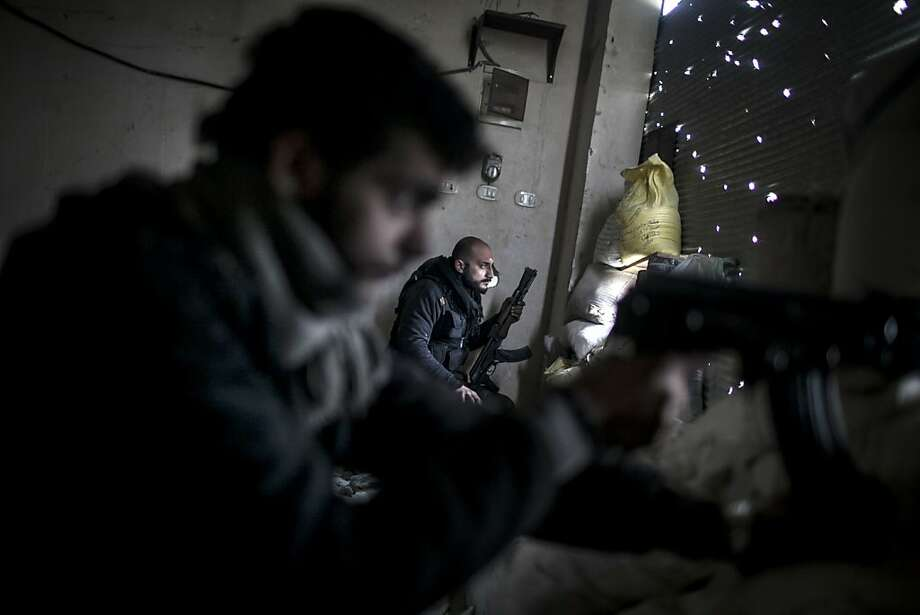 Free Syrian Army fighters hold their weapons during heavy clashes with government forces in Aleppo, Syria, Sunday, Jan. 20, 2013. The revolt against President Bashar Assad began in March 2011with peaceful protests but morphed into a civil war that has killed more than 60,000 people, according to a recent United Nations recent estimate. Photo: Andoni Lubaki, Associated Press