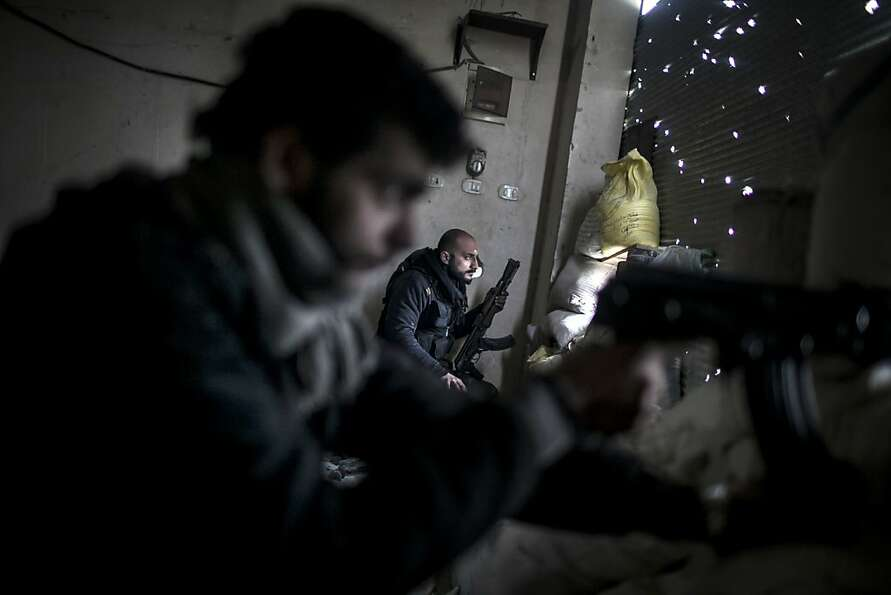 Free Syrian Army fighters hold their weapons during heavy clashes with government forces in Aleppo,