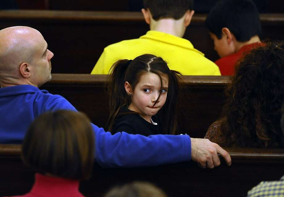 A girl sits with her family in a pew during an interfaith a sermon at Newtown Congregational Church in Newtown, Conn., Sunday, Jan. 20, 2013.  The Rev. James A. Forbes, Jr., who led one of the country's most prominent liberal Protestant churches, is speaking at the church to honor the victims of last month's school shooting and the legacy of the Rev. Martin Luther King Jr. Photo: Jessica Hill, Associated Press