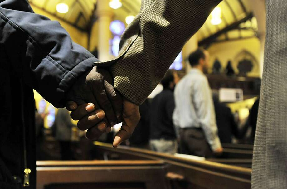 "People hold hands as they sing ""We Shall Overcome"" at the close of the Dr. Martin Luther King, Jr. service at Central United Methodist Church in Detroit on Sunday, Jan. 20, 2013. Photo: Robin Buckson, Associated Press"