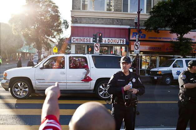 San Francisco police officers keep an eye on the revelry at 24th and Mission streets as 49ers fans celebrate their team's victory on foot and in cars. Photo: Jason Henry, Special To The Chronicle
