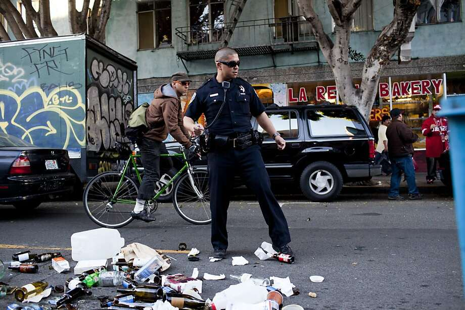A SFPD officer swept broken glass out of the street after a fan threw a trash can into the middle of 24th Street during celebrations after the San Francisco 49er's beat the Atlanta Falcons and was promptly arrested by SFPD in San Francisco, Calif., Sunday, January, 20, 2013. Photo: Jason Henry, Special To The Chronicle
