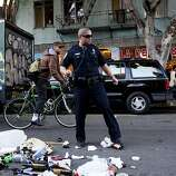 A SFPD officer swept broken glass out of the street after a fan threw a trash can into the middle of 24th Street during celebrations after the San Francisco 49er's beat the Atlanta Falcons and was promptly arrested by SFPD in San Francisco, Calif., Sunday, January, 20, 2013.