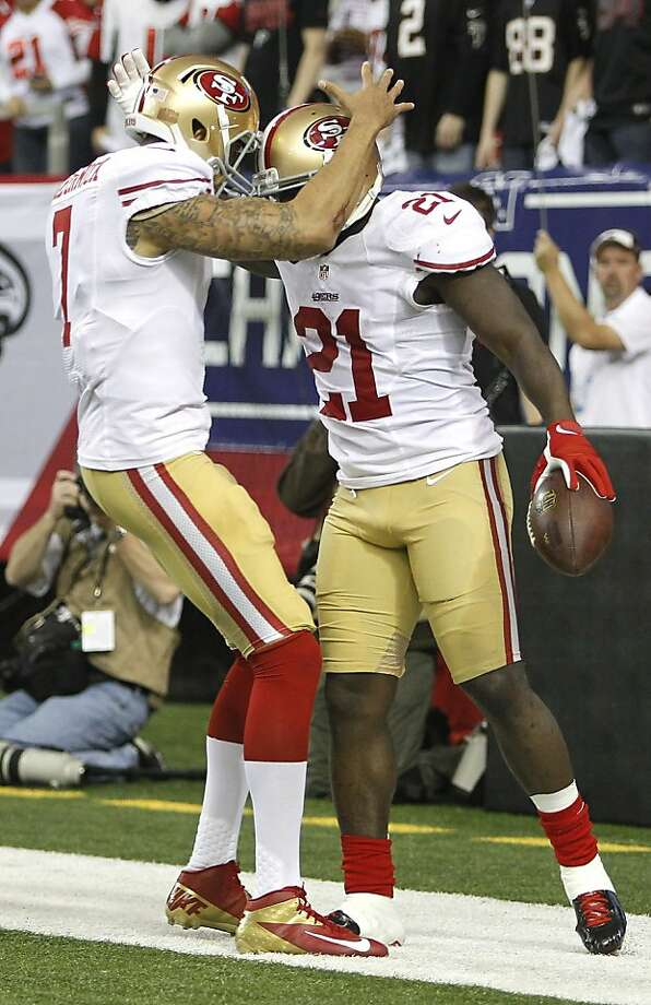 Story with legs: Colin Kaepernick greets Frank Gore, who was fined for wearing his socks too low. Photo: Michael Macor, The Chronicle