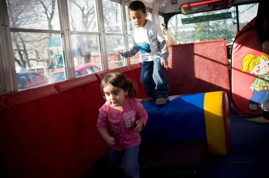 Jaidin Lesperance, 3, right, and Brianna Natalie, 2, left, play on the TumbleBus which visits their day-care center in Norwalk, Conn. on Tuesday, Dec. 22, 2009. Photo: Chris Preovolos / Stamford Advocate