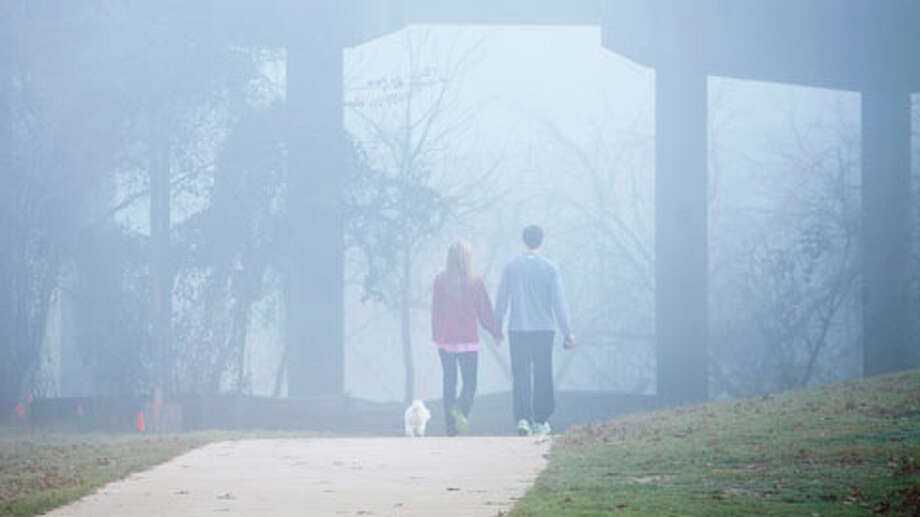 Sarah Grace, left, and Alden Harris take a morning walk along Allen Parkway as fog encapsulates the morning Jan. 20, 2013 in Houston. Photo: Eric Kayne, . / © 2013 Eric Kayne