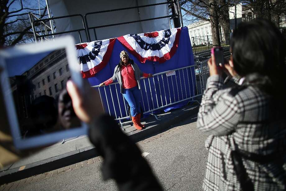 Yvette Adams poses in front of inaugural bunting as Washington prepares for U.S. President Barack Obama's second inauguration on January 20, 2013 in Washington, DC. One day before the public inaugural ceremony at the U.S. Captiol on January 21, Obama was officially sworn in for his second term during a private ceremony surrounded by friends and family in the Blue Room of the White House. Photo: Mario Tama, Getty Images / 2013 Getty Images